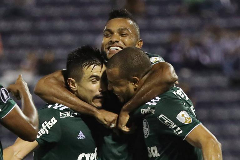 Jogador Borja, do Palmeiras, sorri por ter marcado um gol, abraçado a outros dois atletas