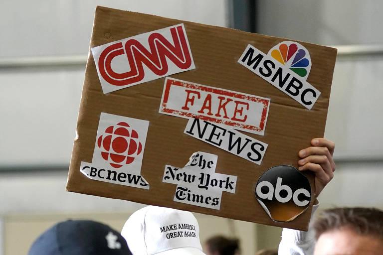 Cartaz mostra nomes de veículos de comunicação e, no centro, as palavras 'fake news' durante discurso em Washington do presidente dos EUA, Donald Trump