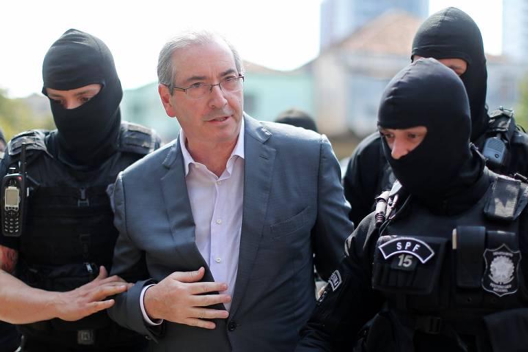 Eduardo Cunha chega à prisão, em outubro de 2016; versão atual do aplicativo não tem o nome do político porque ele não tem mais mandato