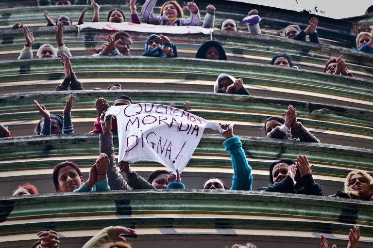 Sem-teto acenam e mostram mensagem com pedido de moradia digna após invadirem prédio na av. Ipiranga no centro de São Paulo