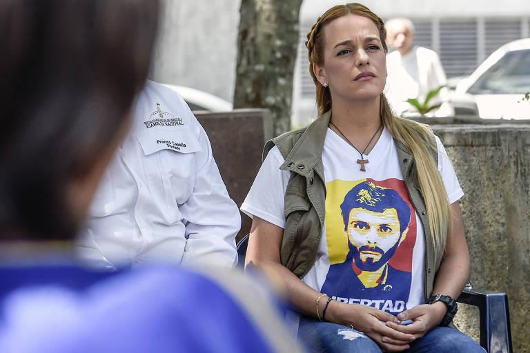 De longe, por trás de uma mulher de cabelo curto, Lilian Tintori aparece sentada com uma camiseta branca com uma foto estilizada de Leopoldo López com as cores da bandeira da Venezuela