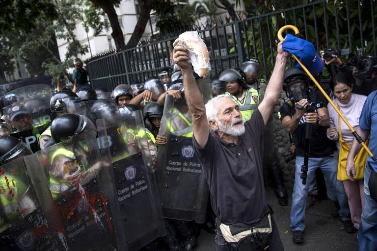 Cercado por tropa de choque, homem segura bengala e pedaço de pão na Marcha dos Avós, ato da série de protestos contra Nicolás Maduro de 2017
