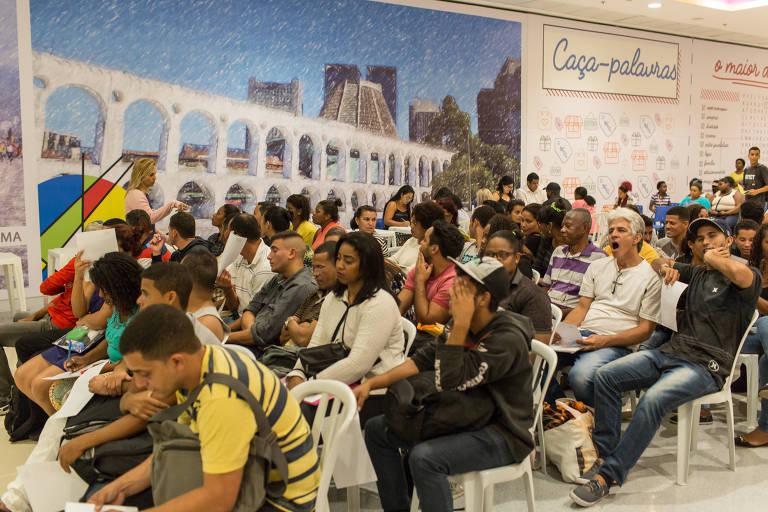 Pessoas aguardam sentadas para preencher ficha e tentar uma oportunidade de emprego no Rio de Janeiro