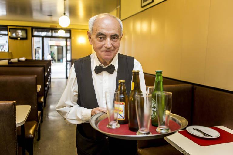 Luiz Domingues, garçom do La Farina, segura uma bandeja com bebidas no salão do restaurante