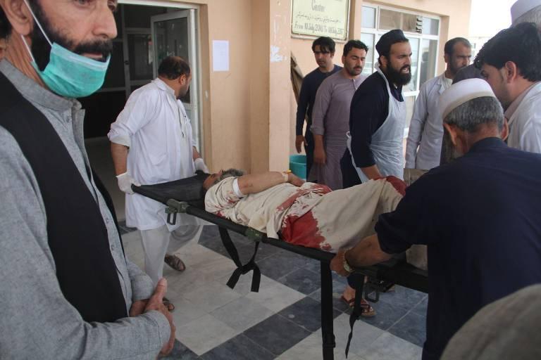 Um homem afegão baleado é levado de maca para um carro para ser encaminhado ao hospital, depois de um atentado em uma mesquita, que também funcionava como centro para registro eleitoral