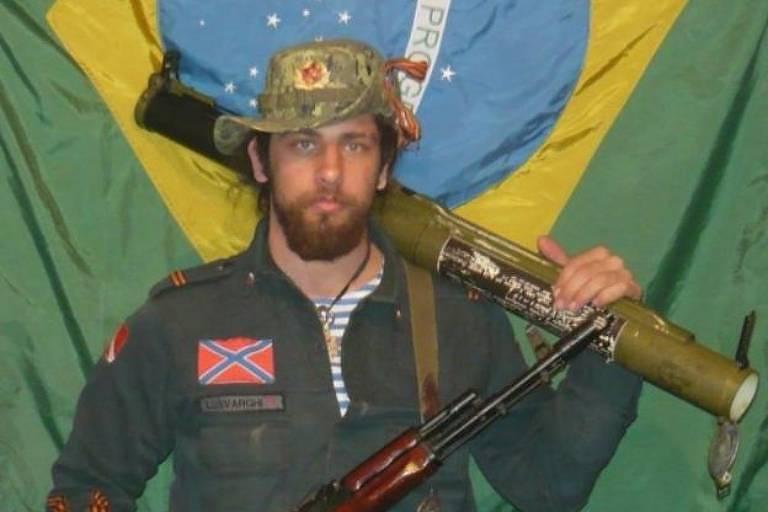 O guerrilheiro brasileiro Rafael Lusvarghi segura armas em frente à bandeira brasileira