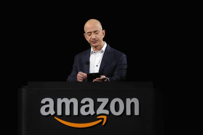 O presidente da Amazon Jeff Bezos, em um palanque com o logo da marca e fundo preto, mexe em um Kindle Fire