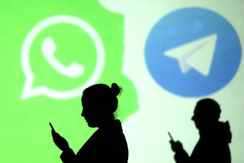 REFILE - CLARIFYING CAPTION Silhouettes of mobile users are seen next to logos of social media apps Signal, Whatsapp and Telegram projected on a screen in this picture illustration taken March 28, 2018.  REUTERS/Dado Ruvic/Illustration ORG XMIT: DAD132