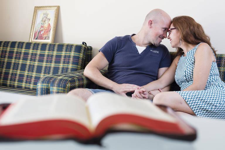 Casal se olha. Eles estão sentados no sofá e há uma Bíblia em primeiro plano
