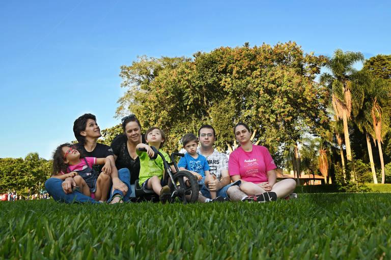 Pais e filhos sentados em gramado
