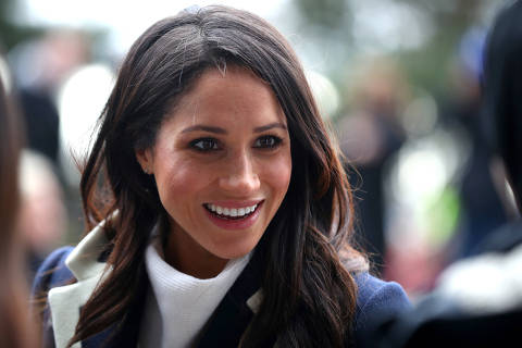 (FILES) In this file photo taken on March 8, 2018 Britain's Prince Harry's fiancee US actress Meghan Markle greets well-wishers as she arrives with the prince at Millennium Point to attend an event hosted by social enterprise Stemettes to celebrate International Women's Day in Birmingham. Raised in Hollywood, she graduated from Northwestern University in theatre and international relations. She made her name starring as Rachel Zane in the US legal drama television series