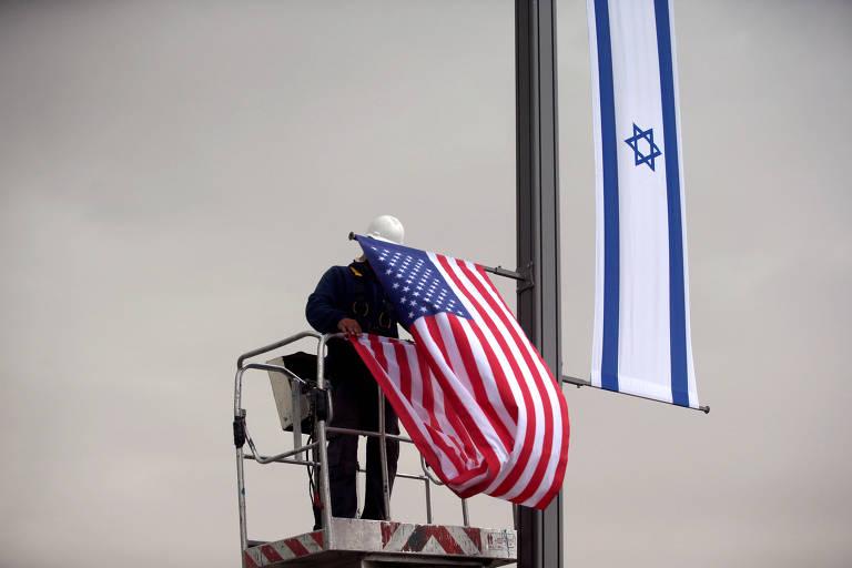 Trabalhador coloca bandeira americano ao lado da de Israel perto da entrada no consulado dos EUA em Jerusalem