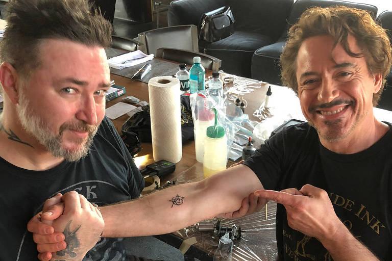 Robert Downey Jr exibe a tatuagem que fez com o símbolo dos vingadores