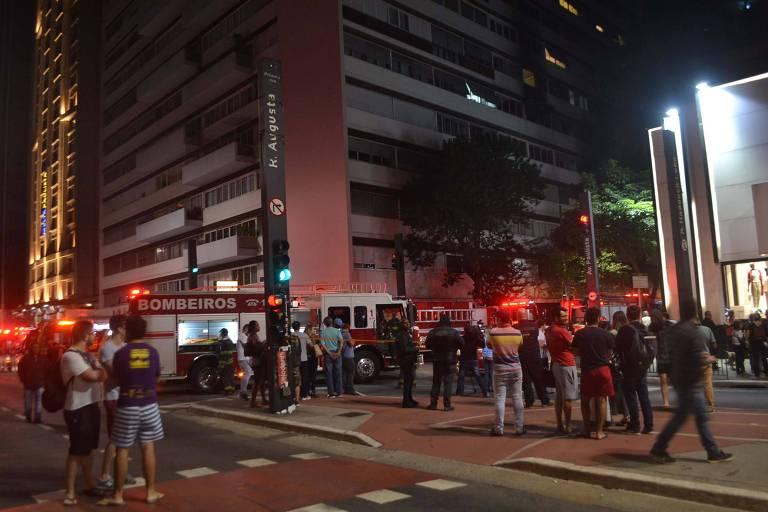 Pessoas se aglomeram em volta de prédio próximo à avenida Paulista que registrou incêndio em apartamento na madrugada desta terça (8)