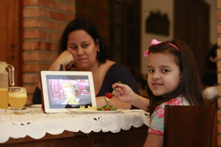 Carol Kolhy tenta tirar a filha Manoela, 8, do tablet durante o jantar