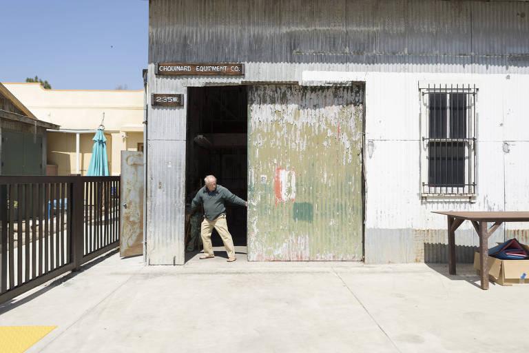 homem abre porta de ferro de armazém
