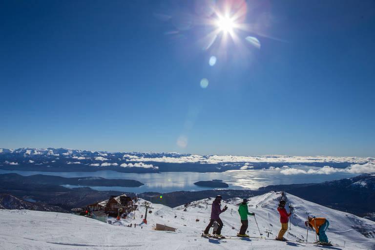 Quatro pessoas com esquis sobre montanha de neve, com céu azul