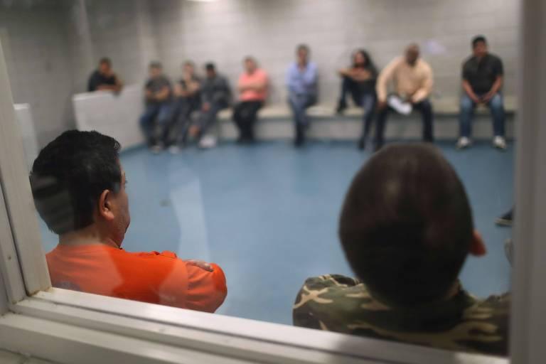 Grupo de pessoas aparece com rosto esmaecido sentadas nos bancos nas laterais de uma sala com bancos brancos encostados na parede branca e com piso azul; eles são vistos por meio do vidro de uma porta
