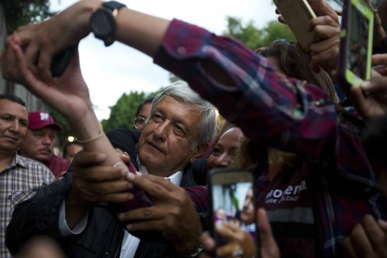López Obrador aparece no meio, ao lado de uma mulher, cujo rosto aparece pela metade e cercado pelos braços de outras pessoas, que carregam celulares; ao fundo outros dois homens acompanham a cena