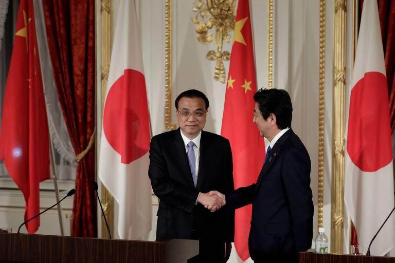 O primeiro ministro japonês, Shinzo Abe (à dir.) e o premiê chinês Li Keqiang anunciam acordo