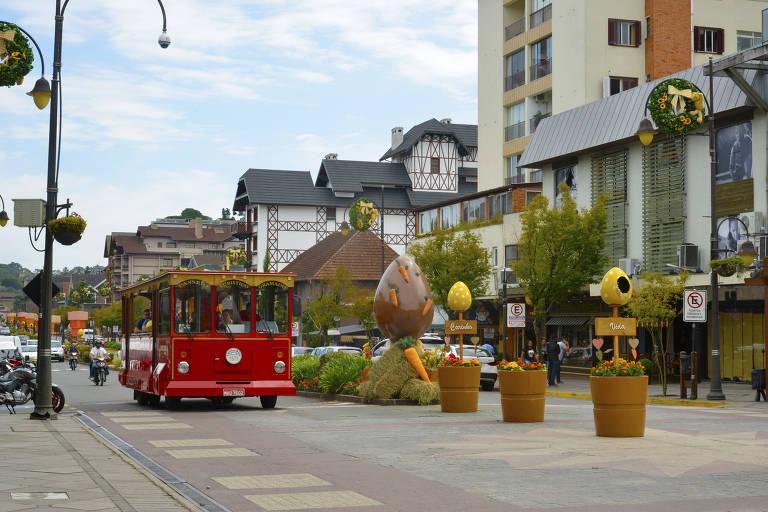 Um ônibus turístico anda no centro de um calçadão em Gramado. A via tem decorações de Páscoa e plantas no centro, e prédios baixos em um dos lados