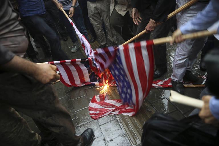 Grupo de quatro pessoas junta paus com bandeiras americanas ao lado de fogo; elas aparecem da cintura para baixo