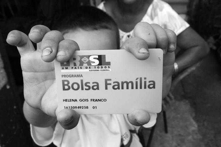 Garoto segura cartão de beneficiária do Bolsa Família, em Ribeirão Preto (SP)
