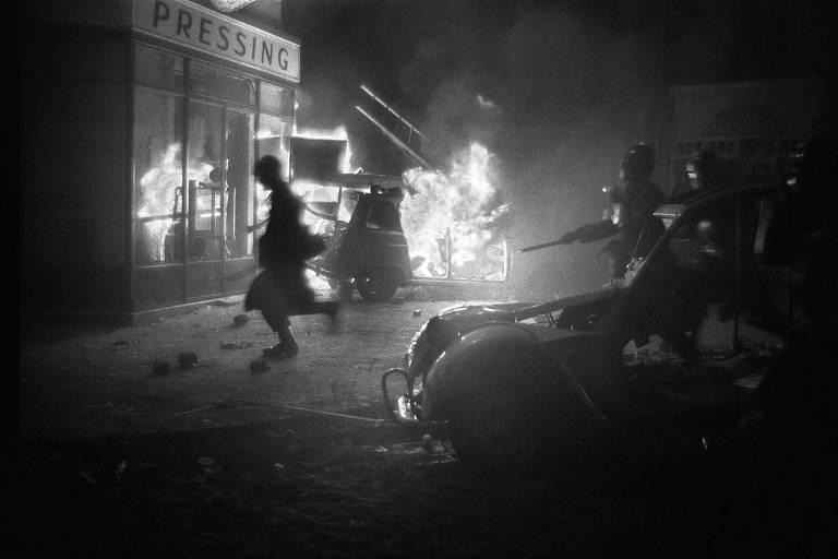 Mulher passa correndo de soldados com armas longas na frente de uma loja; entre eles, um carro queimando