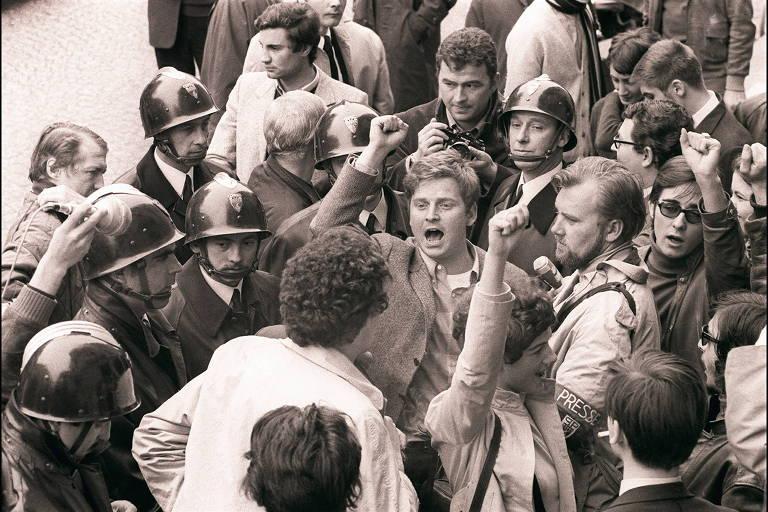 homem em meio a multidão com policiais