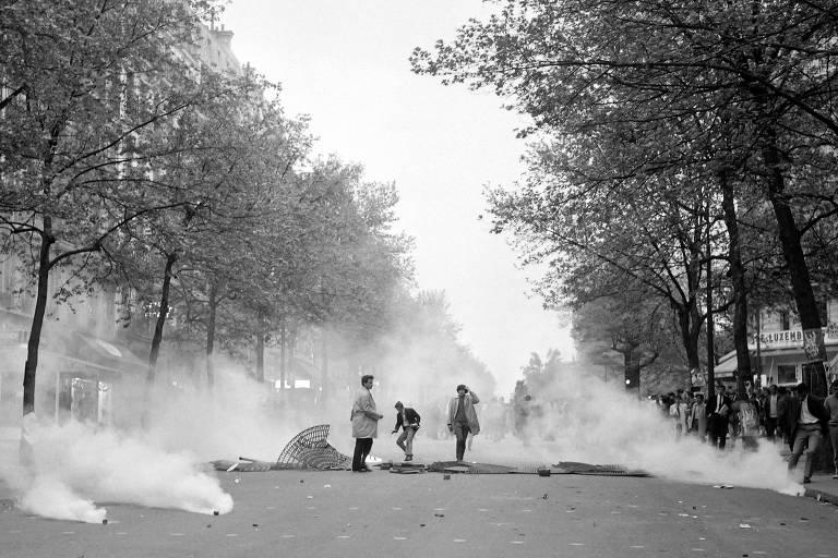 Três homens são vistos em uma avenida de costas lado a lado, sendo que os dois à direita atiram pedras contra um grupo de policiais de tropa de choque à distância; atrás dos manifestantes aparecem uma lata de lixo de ferro retorcida e bombas no chão soltando gás lacrimogêneo