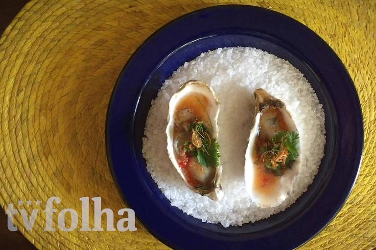 Cena que mostra um prato com ostras sobre uma camada de sal grosso