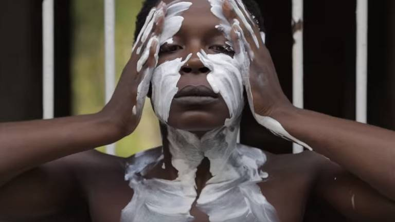 cena em que uma mulher negra se cobre de tinta branca