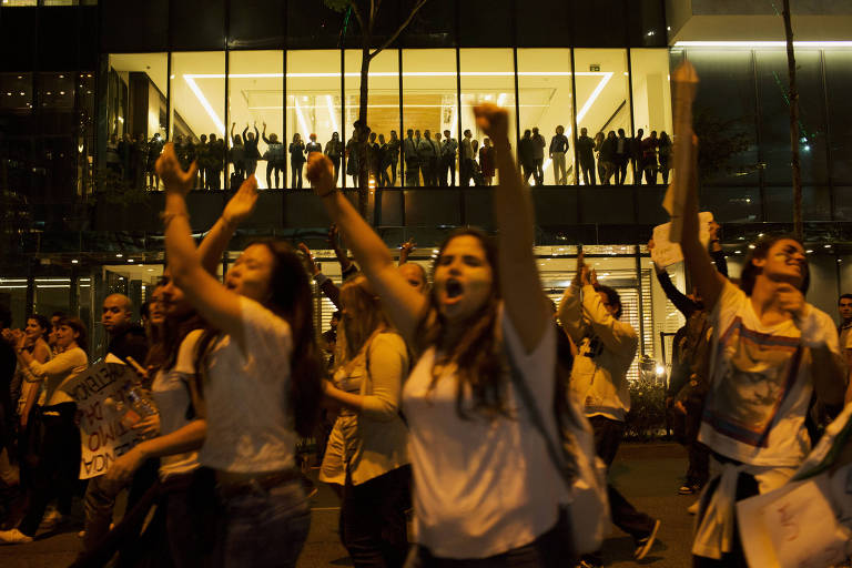 estudantes protestando sob olhar de público em vitrine