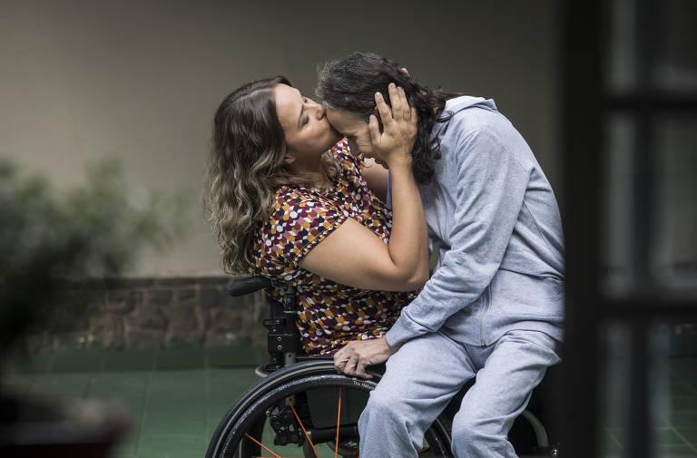 Tabata está sentada em uma cadeira de rodas e veste blusa colorida. Em seu colo, de lado, está a mãe, Eliane, de pijamas, que recebe um beijo na testa da filha