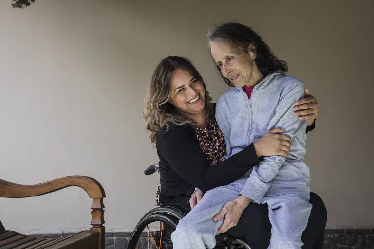 Tabata está sentada em uma cadeira de rodas e veste vestido colorido. Em seu colo, de lado, está a mãe, Eliane, de pijamas, que recebe um beijo na testa da filha