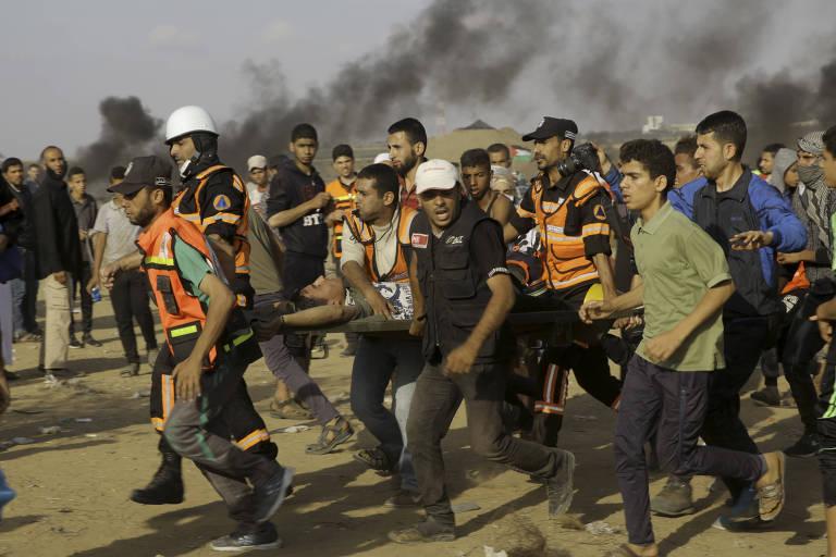 Com coletes refletivos laranja, quatro paramédicos retiram ferido com uma maca, enquanto são acompanhados por cerca de 20 manifestantes, alguns deles usando capacetes; ao fundo, fumaça provocada por pneus queimados