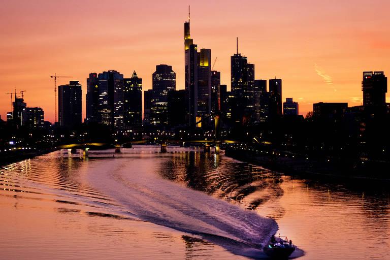 Sombra de arranha-céus durante um pôr do sol em Frankfurt. Em primeiro plano, há um barco navegando no rio Meno