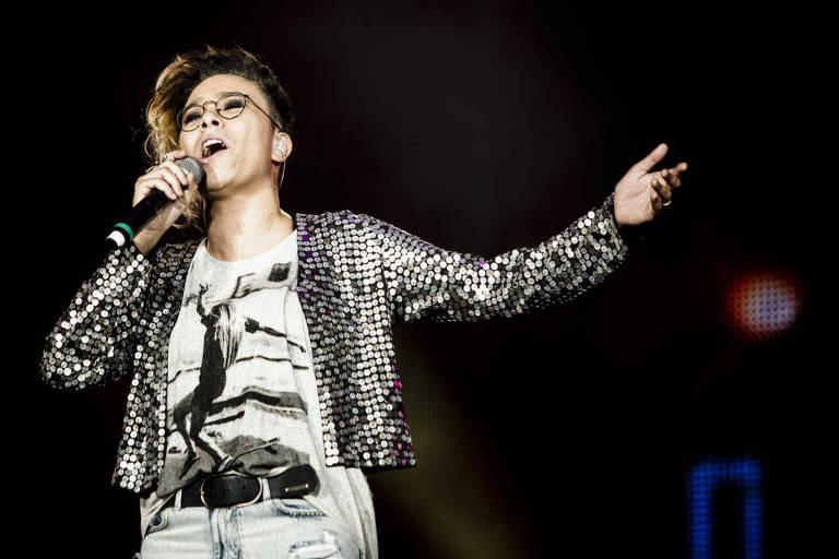 A cantora canta em um palco com um microfone na mão