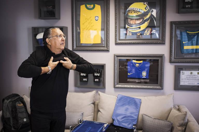 Galvão Bueno, de preto, em pé em seu escritório em SP; ao fundo, camisa da seleção e foto de Senna
