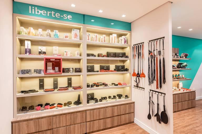 """A loja-conceito da boutique erótica A Sós, toda em tons de azul e branco, com madeira clara e produtos expostos como em uma loja de cosméticos e um letreiro que diz """"liberte-se"""""""