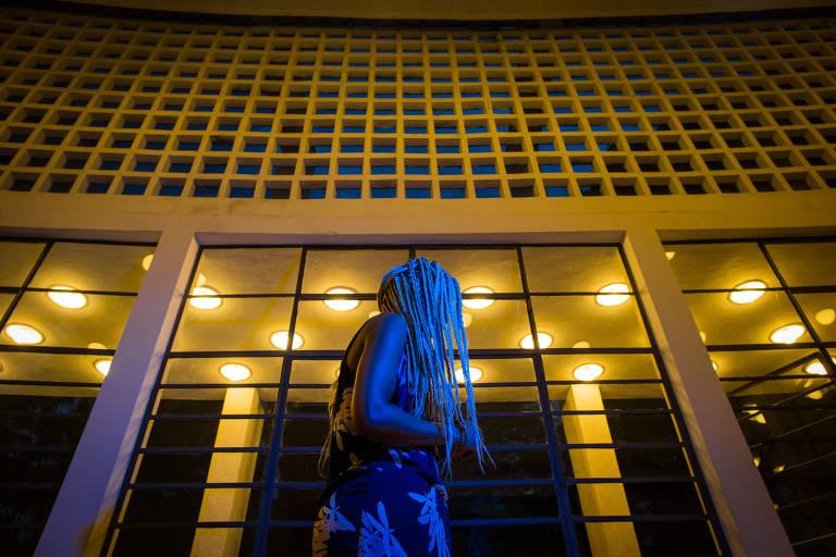 Com tranças, Nduduzo Godensia Diamini aparece sob luz azul de perfil em frente à fachada iluminada do teatro municipal da Mooca, em São Paulo