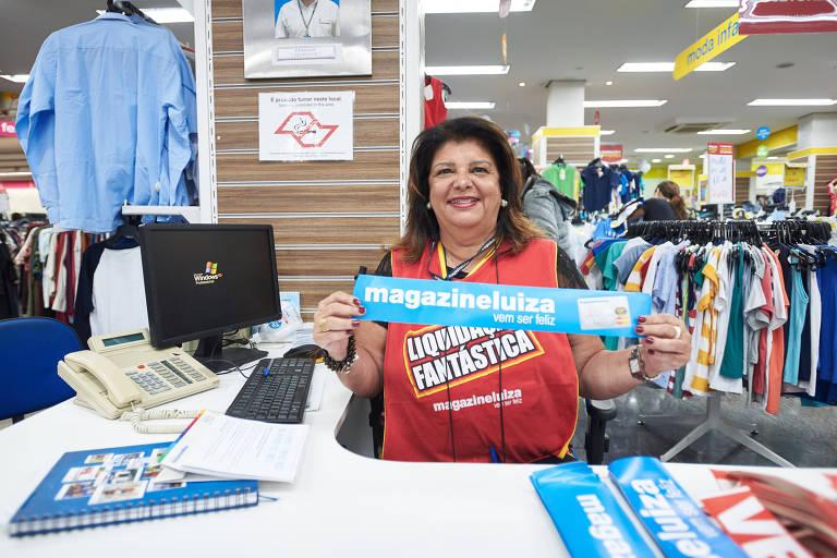 """Retrato de Luiza Helena Trajano em uma loja da Magazine Luiza; a empresária usa uma camiseta personalizada da varejista e segura um papel escrito """"Magazine Luiza: vem ser feliz"""""""