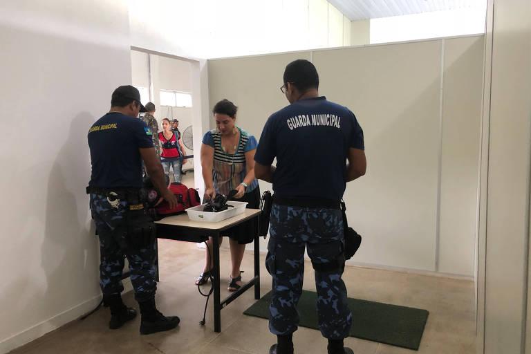 Guardas municipais de São Gabriel da Cachoeira (AM) revistam passageira no aeroporto da cidade