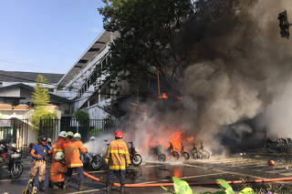 Firefighters try to extinguish a blaze following a blast at the Pentecost Church Central Surabaya (GPPS), in Surabaya, East Java