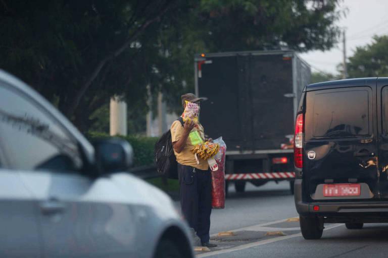 Vendedores ambulantes se arriscam entre os carros na marginal Tiete