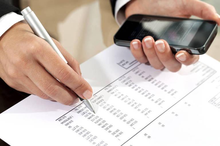 Mulher confere contas com a ajuda do celular