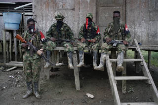 Rebels from Colombia's Marxist National Liberation Army (ELN) rest outside a house near the San Juan river