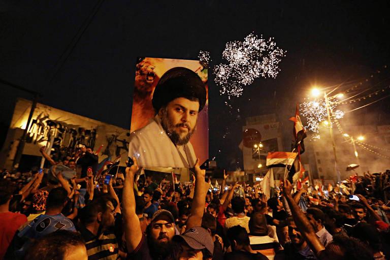 Manifestantes em Bagdá carregam um cartaz de Muqtada al-Sadr logo após a divulgação dos primeiros resultados da eleição