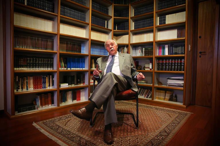 José Gerardo Grossi  está sentado em uma cadeira e atrás dele estão várias estantes com muitos livros