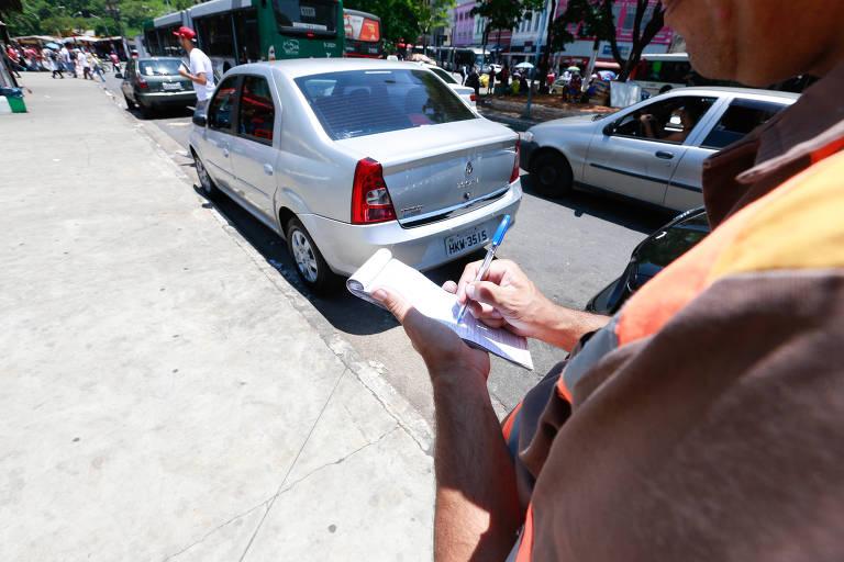 Agente da CET multa carro estacionado em local proibido no centro de São Paulo
